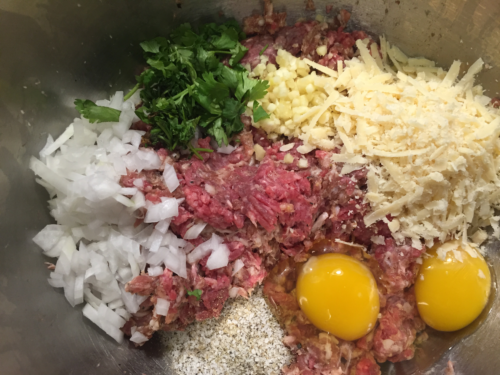 In a large bowl, combine the beef, Italian sausage, garlic, onions, eggs, Parmesan cheese, parsley, salt, pepper and garlic powder.